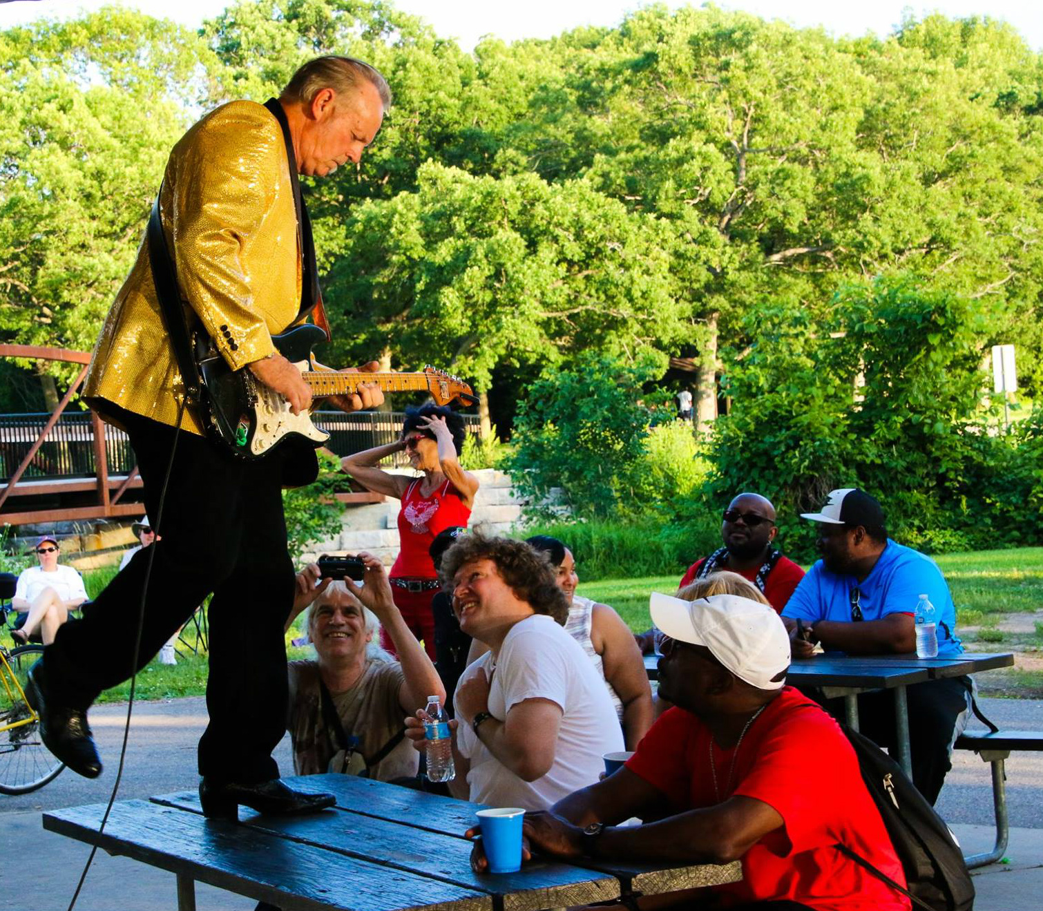 Paul Filopowicz playing guitar in a shiny yellow jacket, dancing on top of a wooden picnic table while he plays. Audience members are smiling up from their seats on the benches, and snapping photos.