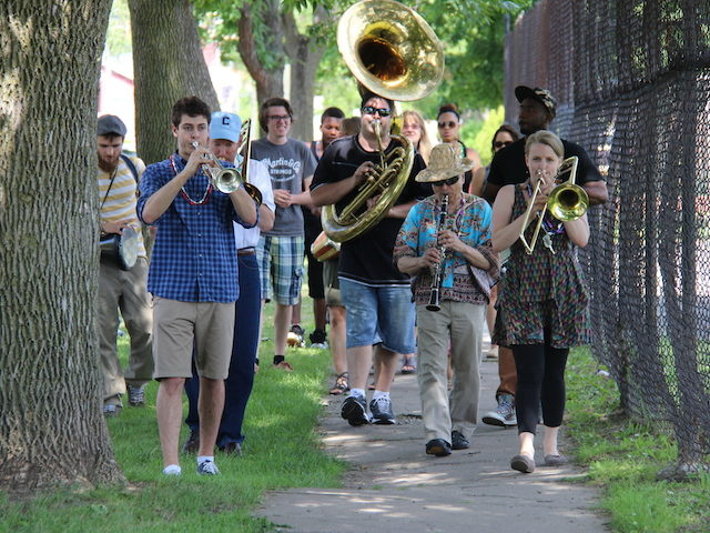 Marching ensemble among trees outdoors