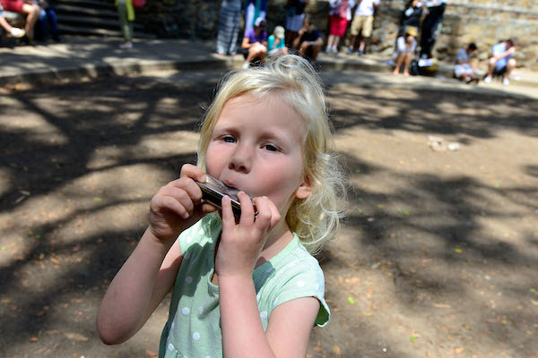Girl playing harmonica at Make Music San Diego