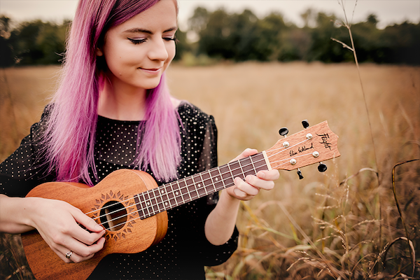 Ukulele player Elise Ecklund plays her instrument in a field