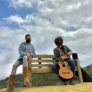 Image of musicians Claire and Theo on a bench with a guitar