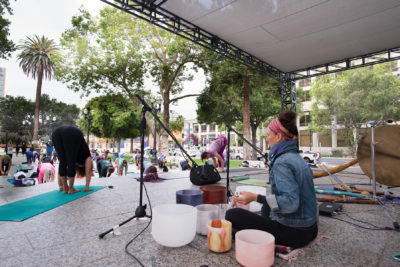 Jessica Neideffer playing crystal bowls while people do yoga in the park