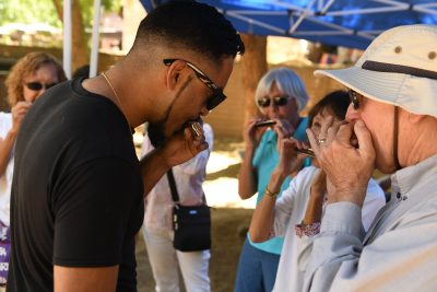 Instructor Aki Kumar demonstrating how to play harmonica to workshop participant.