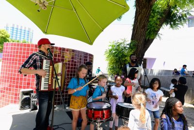 Zydeco player leading children an a music play along with drums and washer boards