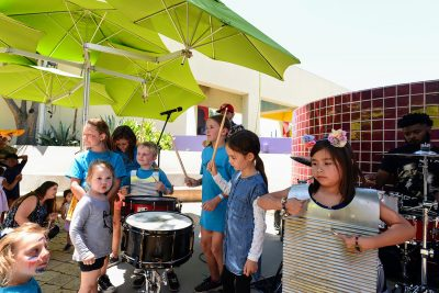 Children playing a variety of music instruments including drums and washer boards