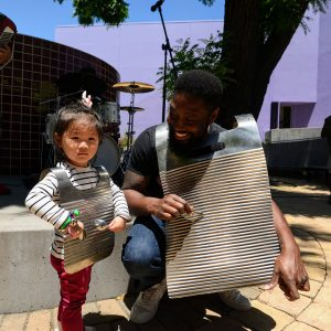Musician wearing washer board with toddler wearing small washer board