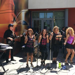 four singers with a band dancing outside community center