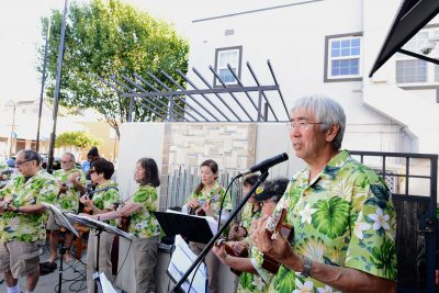 Ukulele band wearing Hawaiian shirt performing on patio of Roy's Station Cafe.