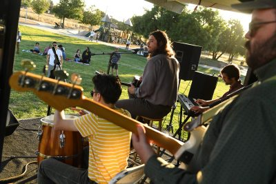 Photo from the stage behind band looking out at audience on grass in the park.