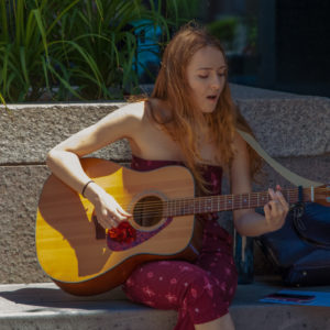 Young woman mid song and strumming her guitar