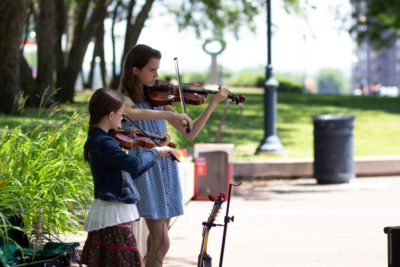 Two young girls play their violins.