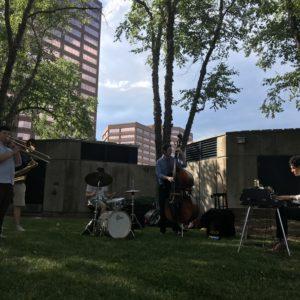 Matt De Leon Quintet perform in the green grass.