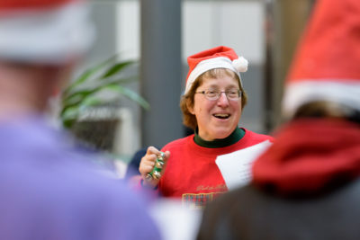 This a picture of a woman with a Santa hat and a dazzling smile.